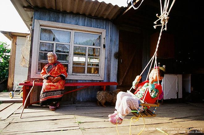 """©2006-2008, ОАО """"Российские железные дороги""""<BR/> ©2006-2008, Антон Ланге<BR/> Два поколения, старшее и младшее, большой нанайской семьи отдыхают на террасе своего дома в Сикачи-Аляне – старинном нанайском поселении в Хабаровском крае. В низовьях Амура и на Сахалине до сих пор живут народы, говорящие на языках тунгусо-маньчжурской группы: орочи, удэгейцы, нанайцы.Малые народности Дальнего Востока и по сей день сохраняют черты коренного уклада жизни, например традиционную одежду – запашной халат, украшенный орнаментом."""