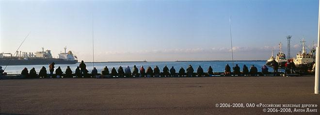 """©2006-2008, ОАО """"Российские железные дороги""""<BR/> ©2006-2008, Антон Ланге<BR/> С рассветом набережную Туапсе заполняют страстные рыболовы. Они рассаживаются вдоль берега – лицом к морю, спиной к солнцу, и их удочки ритмично движутся вверх-вниз, образуя странную, напоминающую гигантского морского ежа фигуру, то и дело шевелящую иглами. Со стороны кажется, что эти глядящие на море люди совершают какой-то таинственный ритуал: снимая добычу с крючка, они склоняют головы, как истовые богомольцы."""