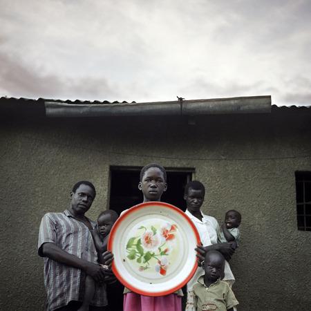 Уганда, лагерь Амага. Chris de Bode. 2004 Агентская традиция съёмки «в лоб».  14-летняя девочка Erin Akullu держит в своих руках единственную вещь, которую ей и её семье позволили забрать, когда они бежали от Армии сопротивления Господа.