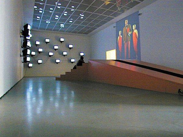 Бьорн Мельхус<br /> Primetime (тираж: 3 + 1) 2001<br /> видеоинсталляция, 11 мин., 29 мониторов, 1 проекция, сцена