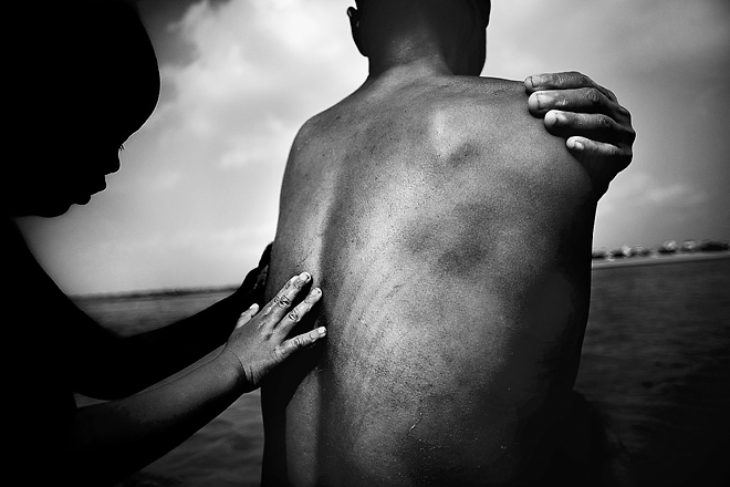 1st prize Daily Life Singles<br /> <b>Justin Maxon</b>, USA, Aurora Photos<br /> <i>Mui, a homeless woman with HIV and her son bathe in the Red River, Hanoi, Vietnam</i>