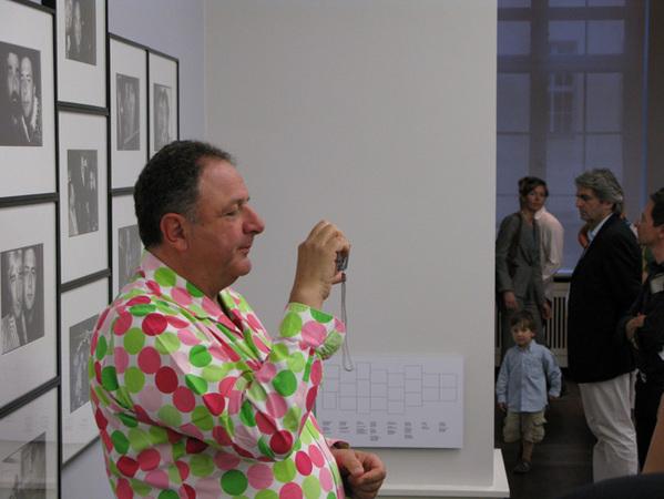 Жан Пигоцци вкрасивой рубашке вкрупный кружочек фотографируют папарацци, которые фотографируют его нафоне его работ.