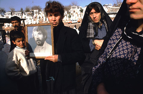 Susan Meiselas. Photographs of 20-year-old Kamaran Abdullah Saber are held by his family at Saiwan Hill cemetery. He was killed in July 1991 during a student demonstration against Saddam Hussein, Kurdistan, Northern Iraq, 1991. © Susan Meiselas/Magnum