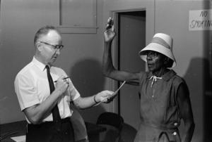 Winfred Moncrief. Voter registration August 25, 1965, at the Magnolia Motel in Prentiss following passage of the Voting Rights Act of 1965. Federal examiner C. A. Phillips administers voter registration oath to Joe Ella Moore. Mississippi Department of Archives and History.