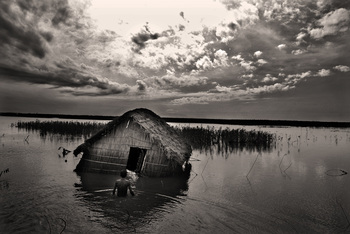 Munem Wasif - Winner Prix Pictet Commission.  Flood waters remain logged. The people have adapted to this aspect of climate and continue to exist in waist-deep flood waters, sometimes even inside their homes. Series: Water Tragedy: Climate Refugee of Bangladesh. Digital Archival Print. 28 x 44 cm. 2007. Chilmari, Bangladesh