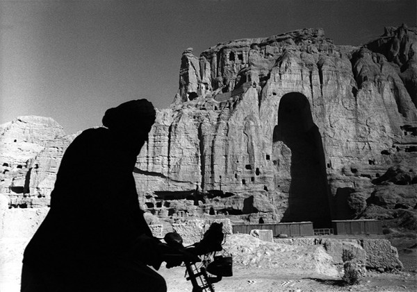 A man cycling past the ruins of the Buddhas of © The New York Public Library, The Miriam and Ira D. 