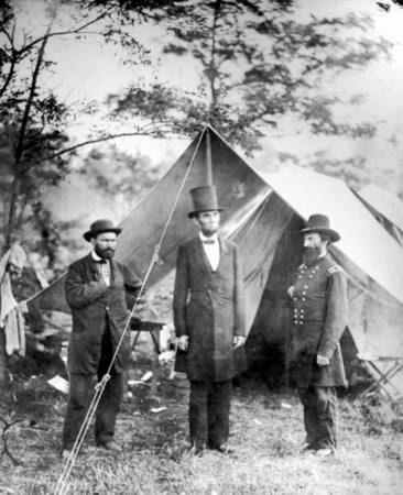 (L-R): Maj. Allan Pinkerton, US Pres. Abraham Lincoln (wearing his trademark stovepipe hat) & Gen. John A. McClernand, in front of pitched tent on battlefield while Civil War is taking place.