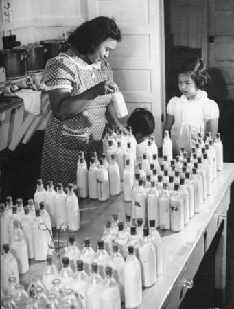 A nurse preparing the children milk at the Hawaiian Nursery. Location: HI, US Date taken: 1941 Photographer: William C. Shrout