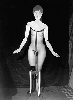 Nude woman body behind a dummy cardboard face on pedestal foot. 1920