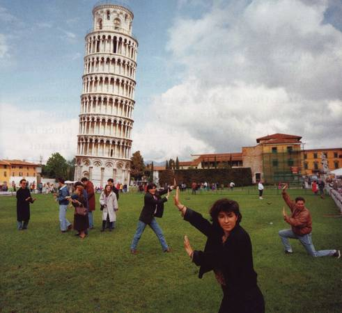 Martin Parr. Pisa, Italy. Several tourists strike the favorite pose in front of the Leaning Tower. 1990