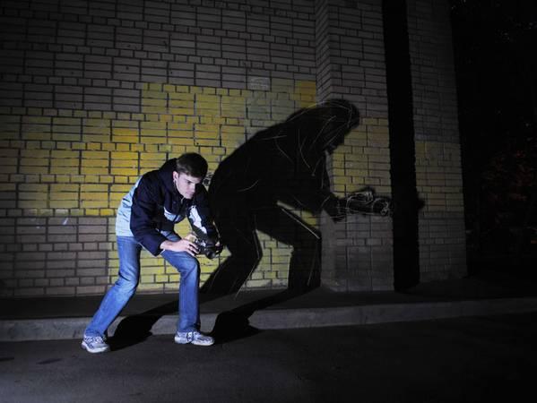 Дмитрий Володин <br />  Стрит-шот <br />  2010<br />  Цифровая  печать <br /><br />  Работа представляет собой серию фотографий, где с  помощью театра теней раскрывается несоответствие между реальным человеком с фотоаппаратом и его образом в общественном сознании. Свет прожектора выхватывает фигуру фотографа, занятого съемкой, но тень на стене рисует за его спиной образ террориста, вооруженного винтовкой, бомбой, гранатой и другими видами оружия.