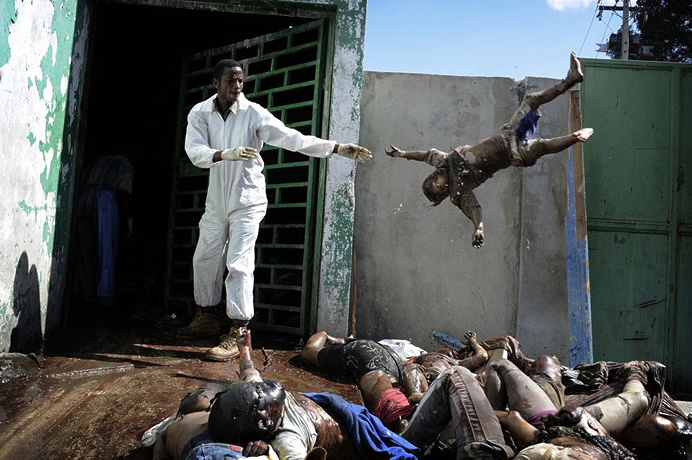 1st Prize General News Stories  Olivier Laban-Mattei, France, Agence France-Presse Haiti earthquake aftermath, 15-26 January A man throws a dead body at the morgue of the general hospital, Port-au-Prince, 15 January