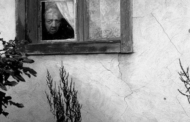 © Petrut Calinescu. Пожилая женщина в черной одежде вдовы смотрит из окна ее дома, Бистрица.