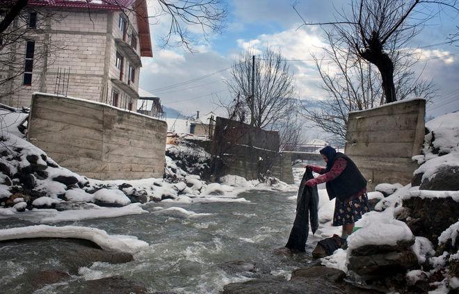 © Petrut Calinescu. Женщина полощет белье в замерзающей  воде речки в деревне Ботиза.  Почти все молодые люди отсюда уехали работать во Францию.