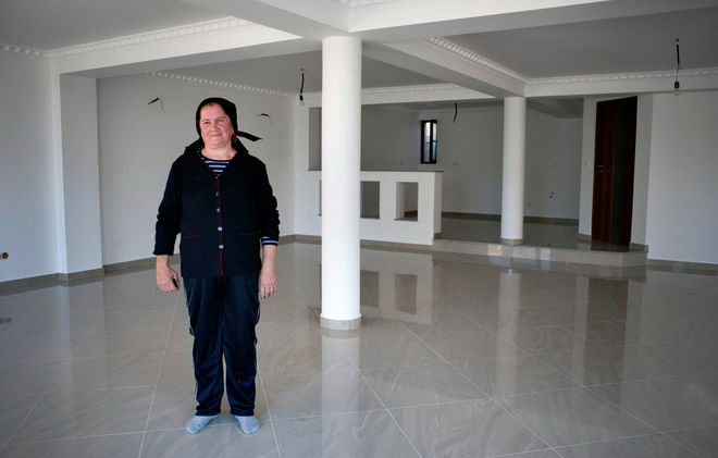 © Petrut Calinescu. Балта Флоаре из Чертезе гордо демонстрирует  кухню в американском стиле и  мраморный пол в доме ее дочери, которая уехала в Париж работать в пекарне.