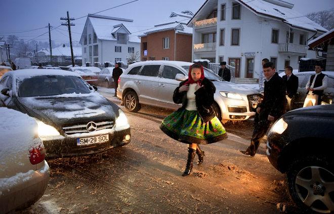 © Petrut Calinescu. Женщина, идущая на свадебную вечеринку. Почти все молодые люди, которые  уезжают работать во Францию и  возвращаются только на праздники, стремятся  показать успех своего пребывания за рубежом — новый традиционный костюм может стоить до 8000 евро.