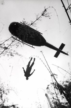 Henri Huet, The body of an American paratrooper killed in action in the jungle near the Cambodian border is raised up to an evacuation helicopter, Vietnam, 1966, gelatin silver print, printed 2004, the MFAH, museum purchase. © Associated Press