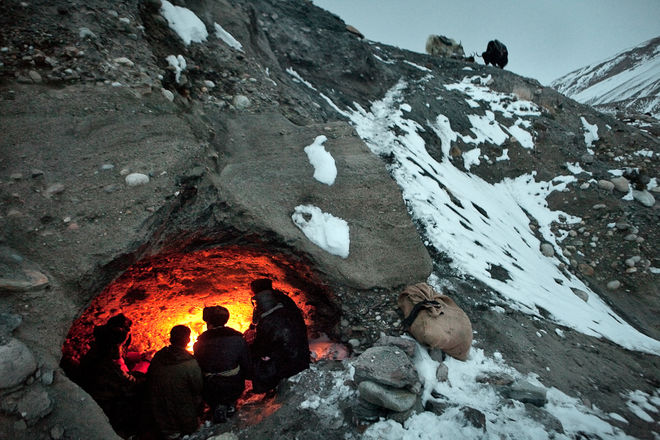 Above the frozen river, a natural cave provides shelter from the cold winter night near Baharak, High Pamir, Afghanistan. © Matthieu Paley