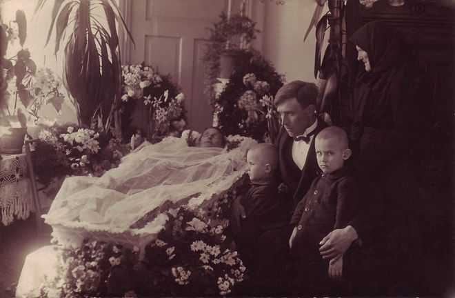 A powerful composition showing a Russian, possibly German, family beside the open casket of the dead mother.