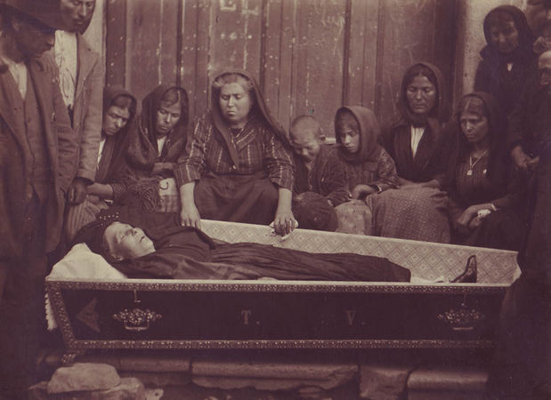 A group of mourners beside the open coffin of an old woman.