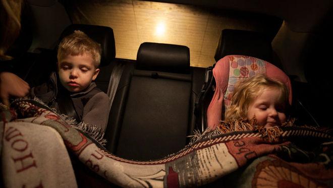 Сара Лейковиц / Getty Images. Дети, отец которых был арестован, едут с мамой в машине.