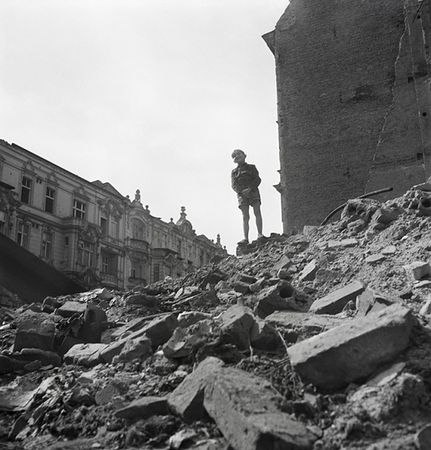 Boy standing on mountain of rubble, Berlin, 1947