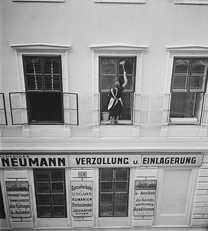 Woman washing windows above Mandtler & Neumann Speditionen, Vienna, 1930s.