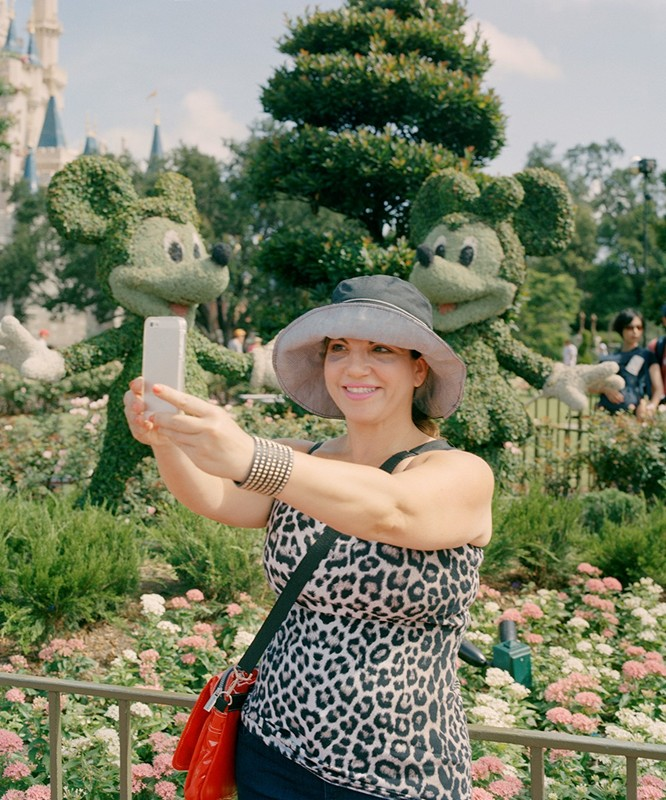 © Molly Matalon. Mom Taking A Selfie In Disney World, 2013