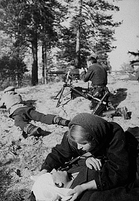 &copy;Михаил Трахман. «Михаил Трахман<br>Санитарка партизанского отряда перевязывает раненного на поле боя<br>Белоруссия, декабрь 1943<br>РГАКФД»