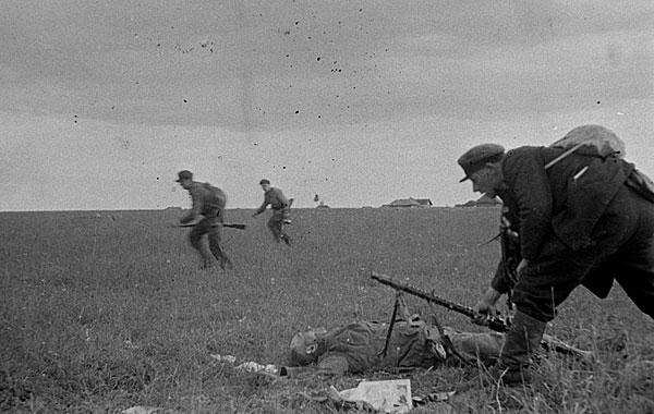 ©Михаил Трахман. «Михаил Трахман<br>Боец партизанского отряда забирает во время боя ручной пулемет у убитого немца<br>Калининская область, 1943<br>РГАКФД»