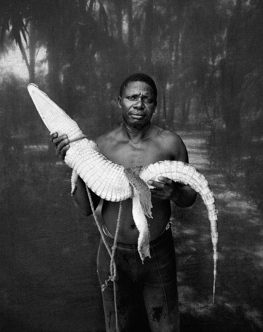 """Джейсон Флорио. «Абду со спасённым крокодилом». Гамбия, Западная Африка, из серии """"Makasutu"""". Когда у Флорио не хватало времени, чтобы ответить на заказы отпечатков, его жена, Хелен Джонс-Флорио, находила возможность взять это в свои руки. © JASON FLORIO"""